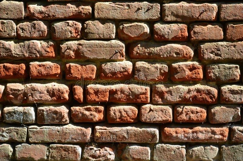 Horizontale muurtextuur van verscheidene rijen van zeer oud die metselwerk van rode baksteen worden gemaakt Verbrijzelde en besch stock fotografie