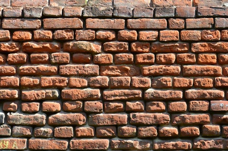 Horizontale muurtextuur van verscheidene rijen van zeer oud die metselwerk van rode baksteen worden gemaakt Verbrijzelde en besch stock afbeelding