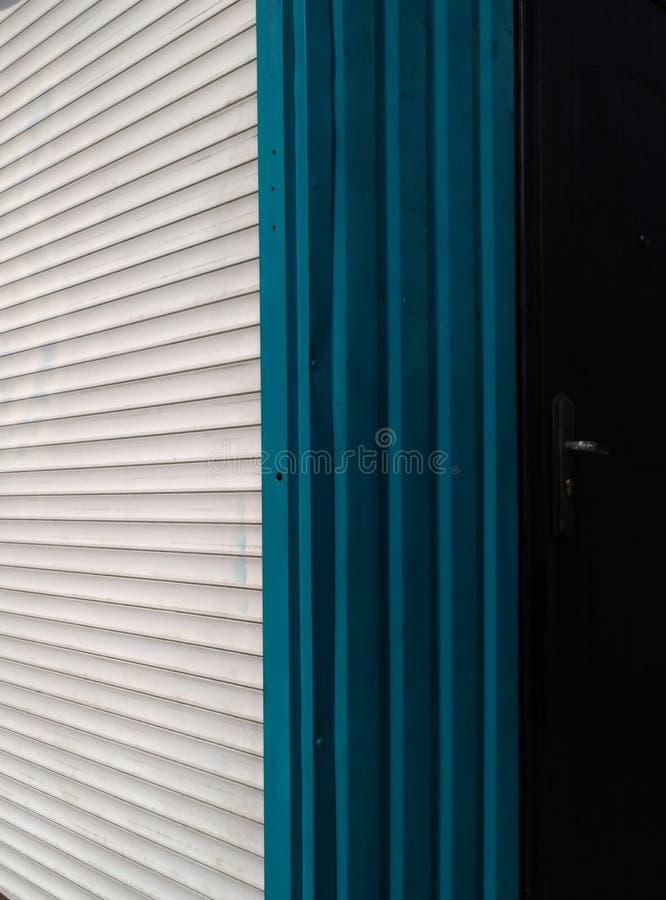 Horizontale und vertikale Streifen von Metallvorhängen mit Tür Vertikales Foto stockfotos
