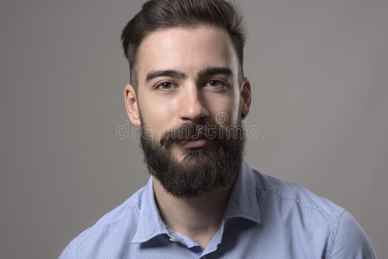 Horizontaler Abschluss herauf Porträt des jungen bärtigen stilvollen Geschäftsmannes im blauen Hemd, das Kamera betrachtet stockbilder