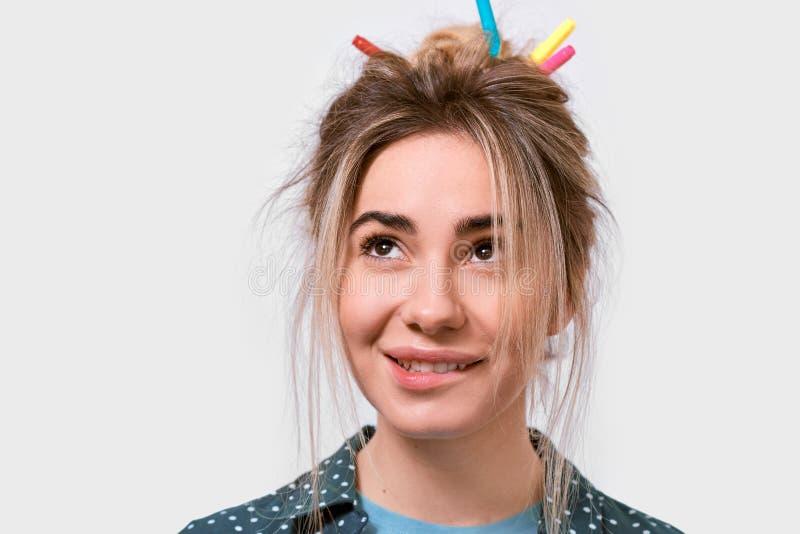 Horizontaler Abschluss herauf Schuss der jungen Frau mit dem wilden Haar, bunte Markierungen im Haar, oben lächelnd und schauen z stockfoto