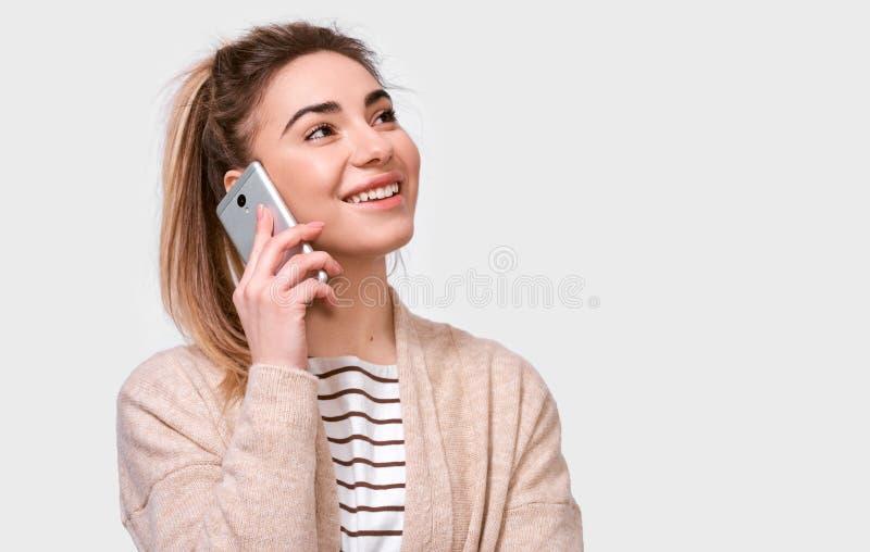 Horizontaler Innenschuß der jungen hübschen Frau, die auf Mobiltelefon mit ihrem Freund, nett und glücklich oben schauend lächelt stockfotografie