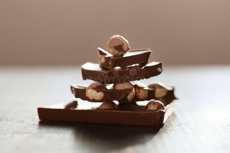 Horizontaler Schuss der braunen Tabelle mit Schokolade, handgemachtes pyramide von chocholate Stücken lokalisiert über dunkler Ob lizenzfreies stockfoto