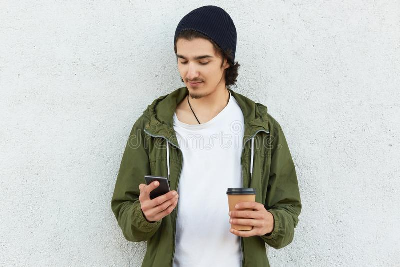 Horizontaler Schuss des attraktiven younsgter in der stilvollen Kopfbedeckung und grüne Jacke, modernes intelligentes Telefon der lizenzfreie stockfotografie