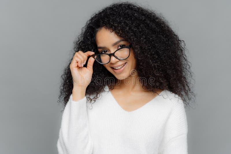 Horizontaler Schuss des erfüllten weiblichen Lehrers hält Hand auf Rahmen von Gläsern, Lächeln glücklich, hat Afrofrisur, trägt z lizenzfreie stockbilder