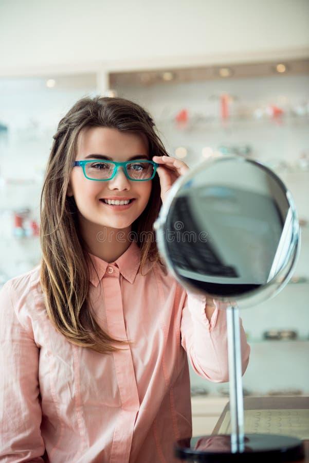Horizontaler Schuss des glücklichen attraktiven Brunette, der neue Gläser für Anblick, seiend glücklich, offenbar zu sehen auswäh lizenzfreies stockbild