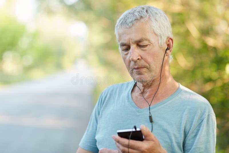 Horizontaler Schuss des hübschen grauen behaarten männlichen Pensionärs hört Radio mit Kopfhörern und Smartphone, benutzt drahtlo stockbild