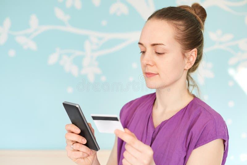 Horizontaler Schuss des jungen weiblichen Modells mit Haarbrötchen, Griffe modernes intelligentes Telefon und Kreditkarte, bestel lizenzfreie stockfotografie