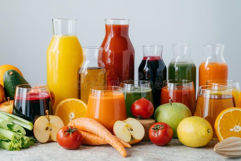 Horizontaler Schuss des zusammengedrückten Gemüses und der Früchte in den Glasflaschen Stellen Sie von den bunten frischen Äpfeln lizenzfreie stockfotografie