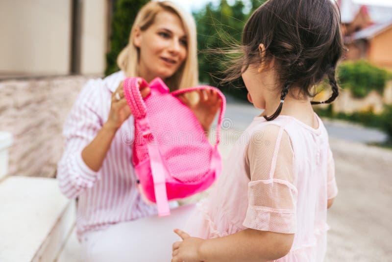 Horizontales Bild der glücklichen überraschten Mutter, die Rucksack vorbereitet, um Rucksack ihrem Kind zum Gehen zum Kindergarte lizenzfreie stockfotos