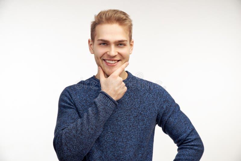 Horizontales fhoto des überzeugten bärtigen Mannes hält Finger auf Kinn, lässt aufmerksamen Blick, kleiden im blauen Pullover lizenzfreie stockbilder
