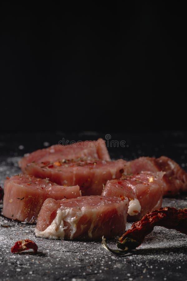 Horizontales Foto des rohen Schweinefiletfleisches Rohes Fleisch ist auf rustikalem dunklem Taktstockbrett, mit Pfeffer und Salz stockfotos