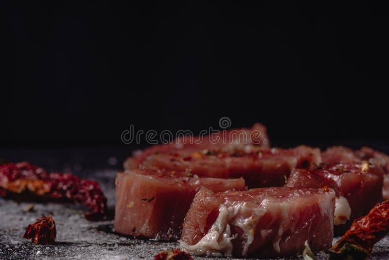 Horizontales Foto des rohen Schweinefiletfleisches Rohes Fleisch ist auf rustikalem dunklem Taktstockbrett, mit Pfeffer und Salz stockfotografie