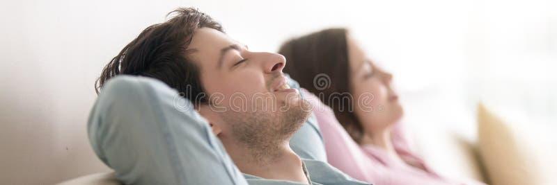 Horizontales Fotoverheiratetes paar mit den geschlossenen Augen, die auf Couch stillstehen lizenzfreies stockbild