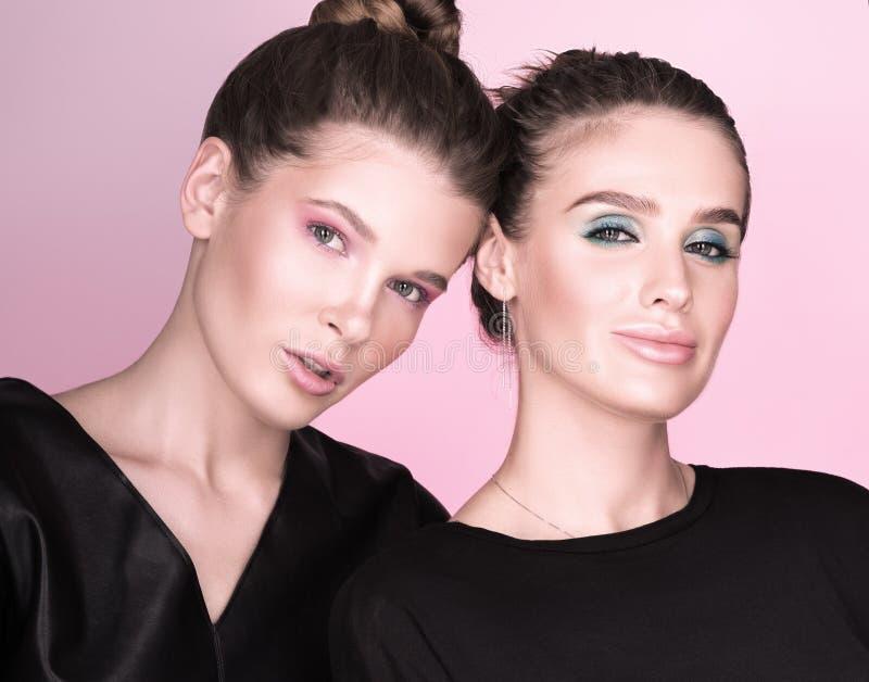 Horizontales Modeporträt Zwei junge Schönheiten im Schwarzen lizenzfreie stockbilder