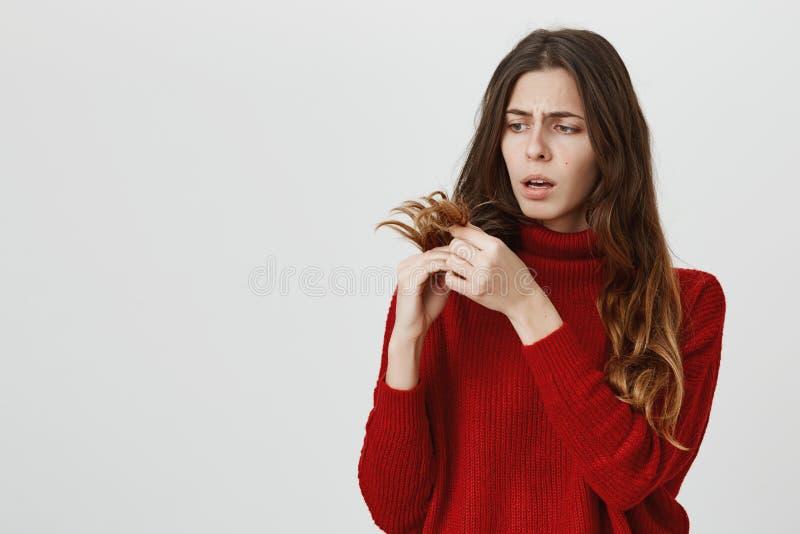 Horizontales Porträt der fassungslosen Frau des Jungeumkippens in der roten Strickjacke, die lang mit traurigem Ausdruck des Gesi lizenzfreie stockfotografie