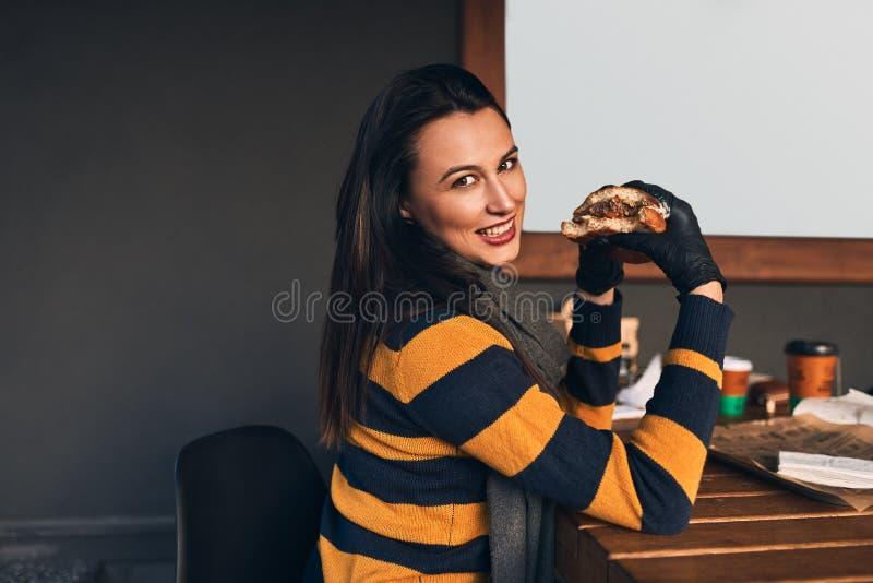 Horizontales Porträt der hungrigen glücklichen Frau, die zufällige Strickjacke, eatting köstlichen Burger beim Sitzen an der Terr stockbild