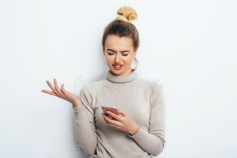 Horizontales Porträt der missfallenen Frau hat empörten Ausdruck, beim Halten von Smartphone, die Stirn runzelt Augenbrauen, kann lizenzfreie stockfotos