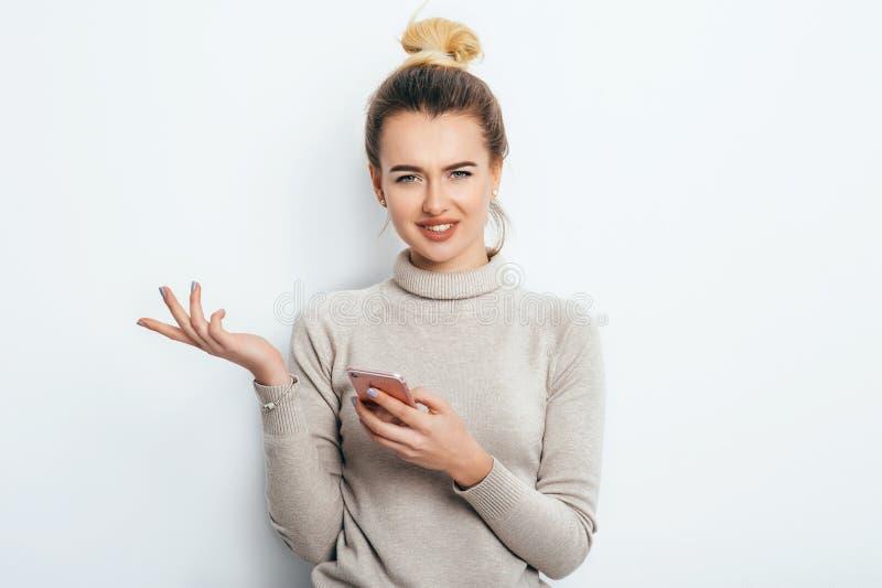 Horizontales Porträt der missfallenen Frau hat empörten Ausdruck, beim Halten von Smartphone, die Stirn runzelt Augenbrauen, kann lizenzfreies stockfoto