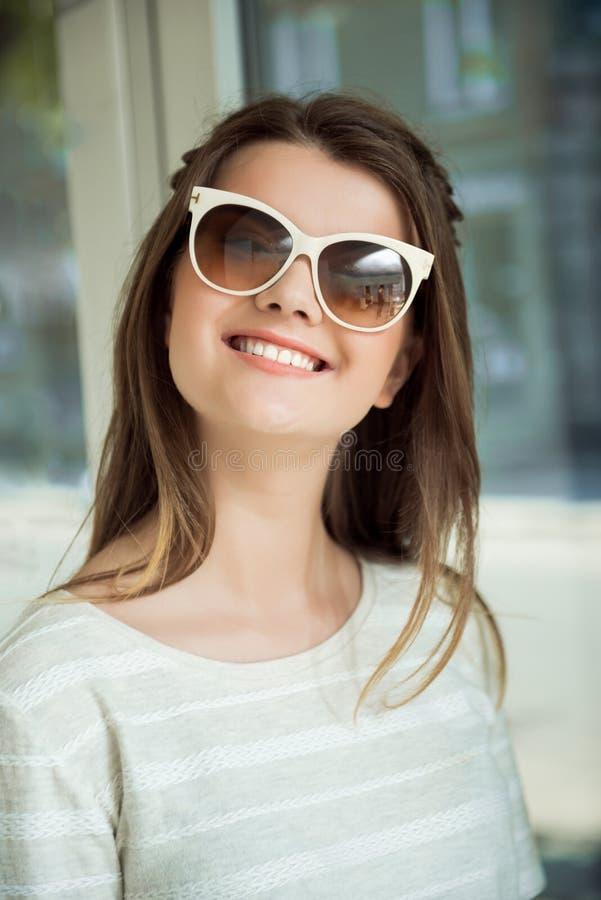 Horizontales Porträt der reizend erfreuten jungen Frau im modernen Eyewear, der an der Kamera aufwirft Mädchen ist mit neuem zufr lizenzfreie stockbilder