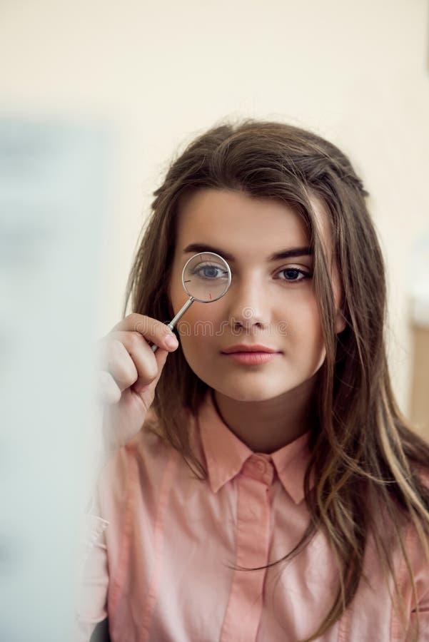 Horizontales Porträt der schönen fokussierten Frau auf Verabredung mit dem Augenarzt, der lense hält und durch schaut lizenzfreie stockfotografie