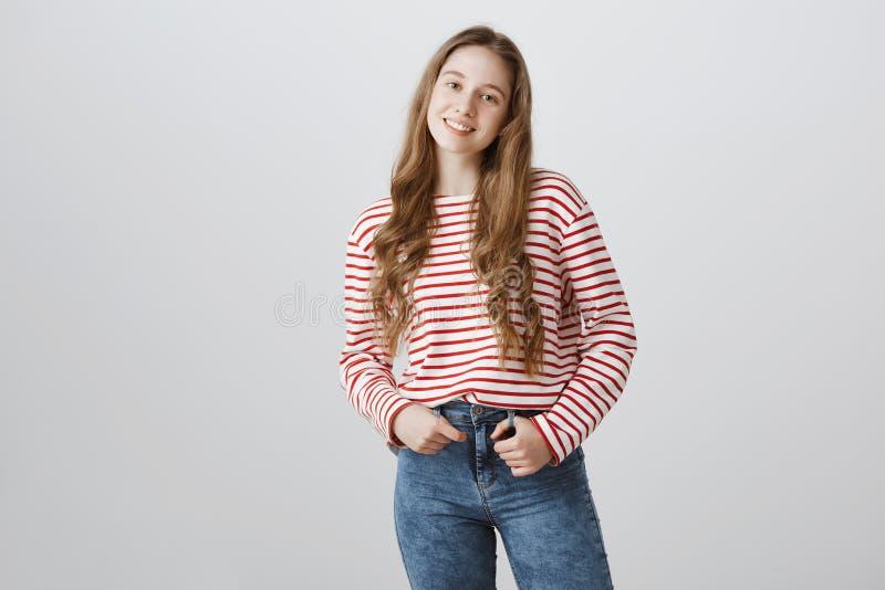Horizontales Porträt des attraktiven jungen europäischen Mädchens mit dem angemessenen Haar in gestreifter Strickjacke breit läch lizenzfreie stockbilder