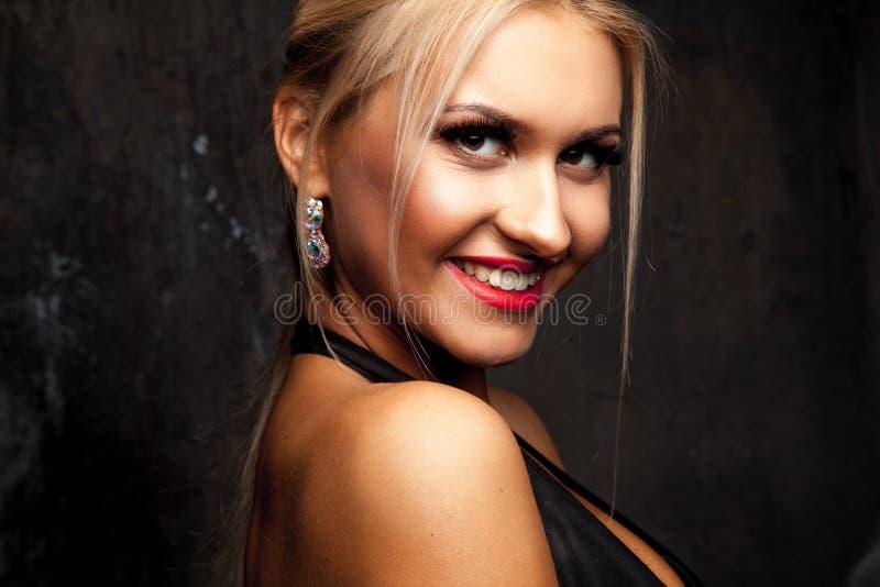 Horizontales Porträt des erwachsenen blonden Mädchens, das an der Kamera lächelt stockfotografie