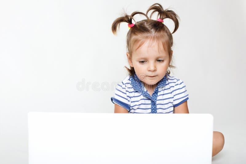Horizontales Porträt des kleinen hübschen Mädchens, das in Laptop-Computer, in interessante Karikatur der Uhren oder in Spielspie lizenzfreie stockfotos