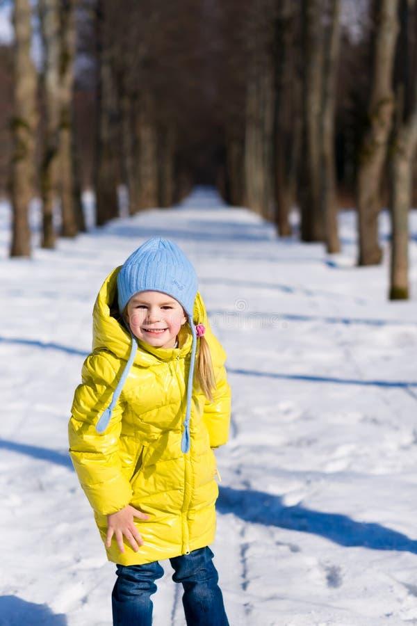 Lustiges kleines Mädchen, das im Winter spielt stockbilder