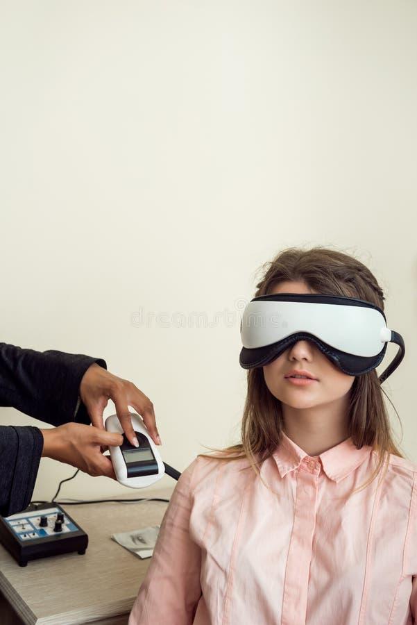 Horizontales Porträt des netten europäischen weiblichen Patienten, der im Ophthalmologebüro, tragende digitale Visionssiebdruckei lizenzfreie stockfotografie