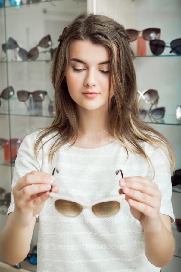 Horizontales Porträt des recht kaukasischen Studenten im Optikerspeicher, der perfekte Paare Sonnenbrille auswählt, um mit ihr zu lizenzfreie stockbilder