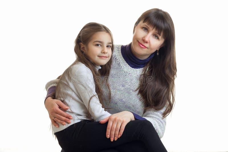Horizontales Porträt einer jungen Mutter mit ihrer netten Tochter lokalisiert auf einem weißen Hintergrund stockfotos