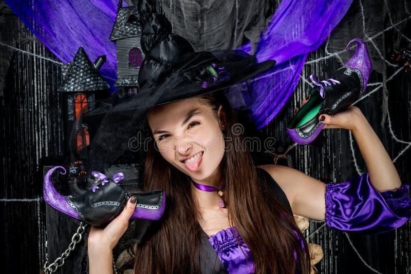 Horizontales Porträt einer netten Hexe mit Schuhen in den Händen stockbild