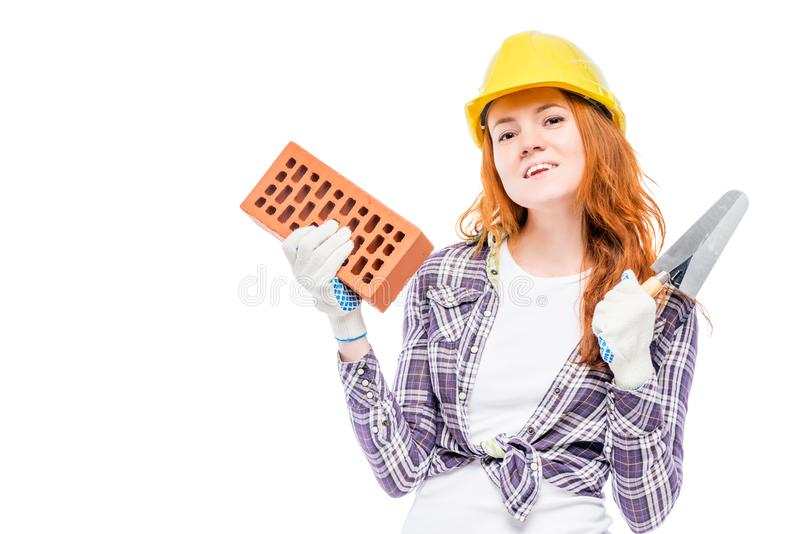 horizontales Porträt eines Frauenerbauers mit einem Ziegelstein und einer Kelle stockfotografie