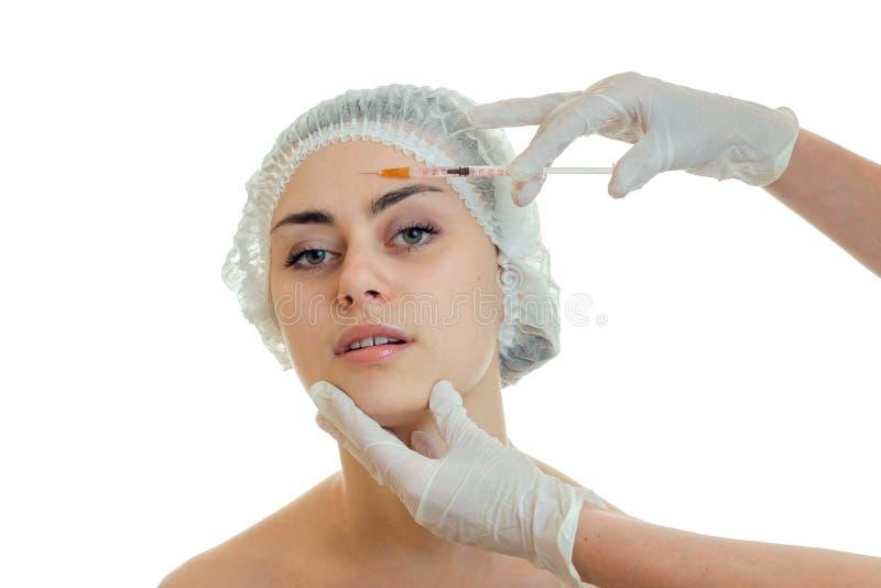 Horizontales Porträt eines jungen Mädchens am Doktor, dem behandschuht Impfstoff auf Gesicht einführt lizenzfreie stockbilder