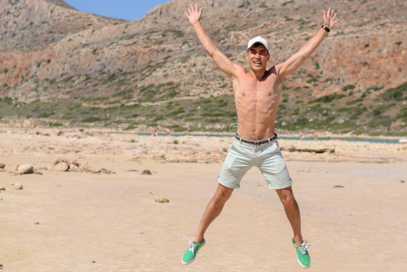 Horizontales Porträt eines jungen Mannes im Urlaub, glückliches Springen oben auf den Strand Kopieren Sie Platz stockfoto