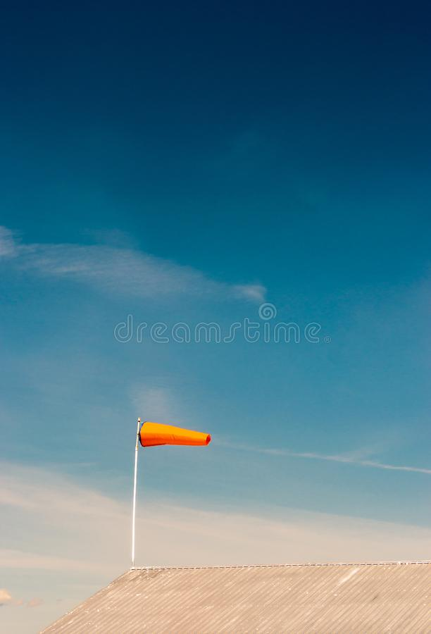 Horizontally flying orange windsock on metal rooftop and clear dark blue sky. royalty free stock photo