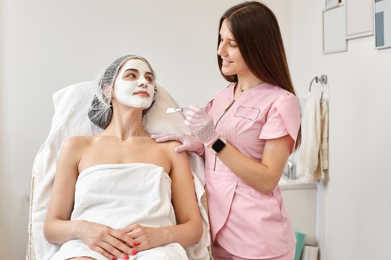 Horizontalshot of beautiful woman receiving spa treatment. Cosmetologist in beauty salon cleaning woman`s face, applying cream stock photo