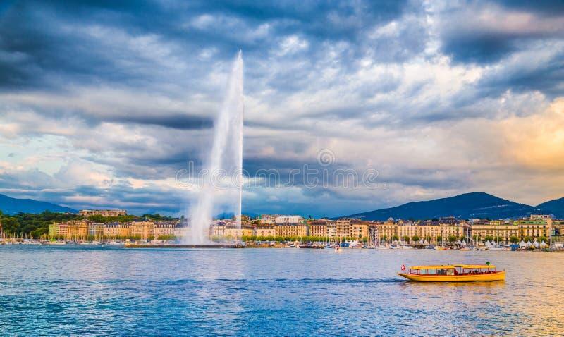 Horizonte de Ginebra con la fuente famosa y el barco del agua del ` del jet d en la puesta del sol imagenes de archivo