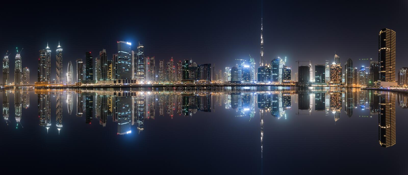Horizonte de la bahía del negocio con la reflexión en el agua en la noche, Dubai, UAE imágenes de archivo libres de regalías