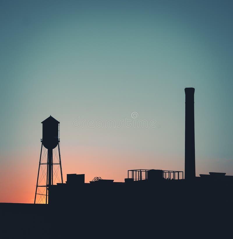 Horizonte de la ciudad con el cielo azul y anaranjado imagen de archivo
