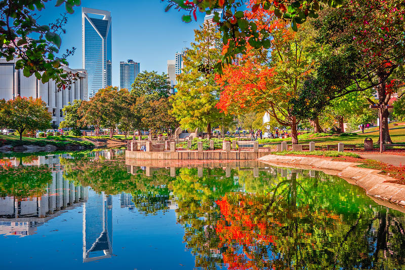 Horizonte de la ciudad de Charlotte a partir de la estación del otoño del parque del ordenar con azul imagen de archivo