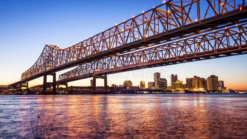 Horizonte de la ciudad de Crescent City Connection Bridge y de New Orleans en el Ni fotografía de archivo