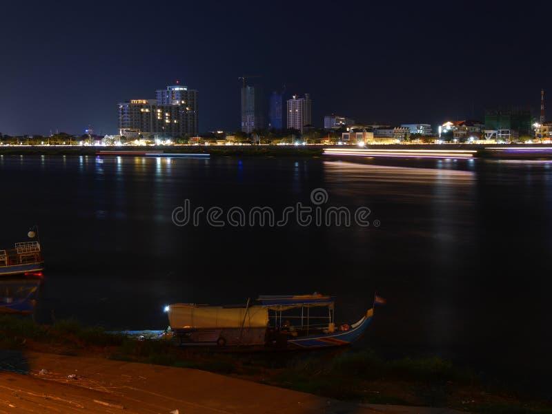 Horizonte de la ciudad de la noche con el barco móvil en el río en frente y un barco foto de archivo