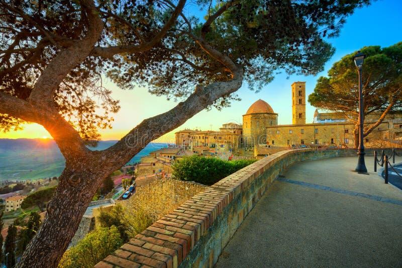 Horizonte de la ciudad de Toscana, de Volterra, iglesia y árboles en puesta del sol ital imágenes de archivo libres de regalías
