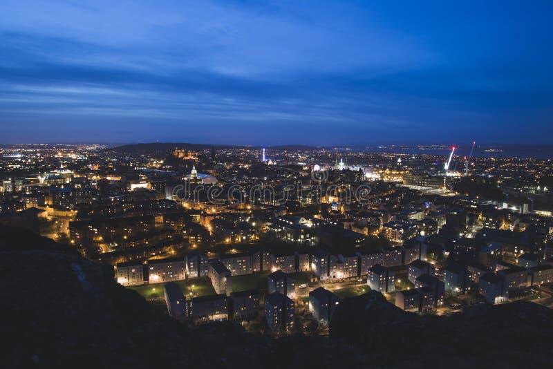 Horizonte de la ciudad de Edimburgo en la noche con los riscos de Salisbury en el primero plano foto de archivo