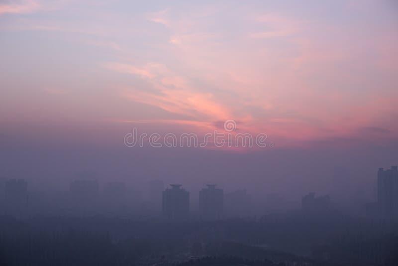 Horizonte de la ciudad en la puesta del sol, porciones de niebla con humo y mala ecología foto de archivo
