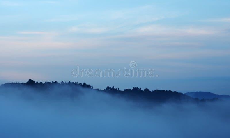 Horizonte de la tarde y valle brumoso fotografía de archivo