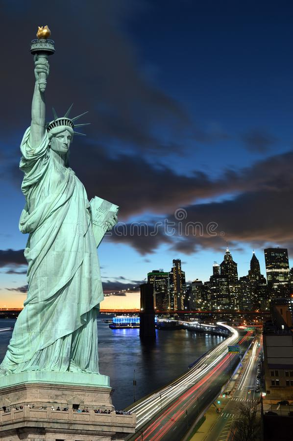 Horizonte de Manhattah con el puente de Brooklyn en la noche y la estatua de la libertad foto de archivo