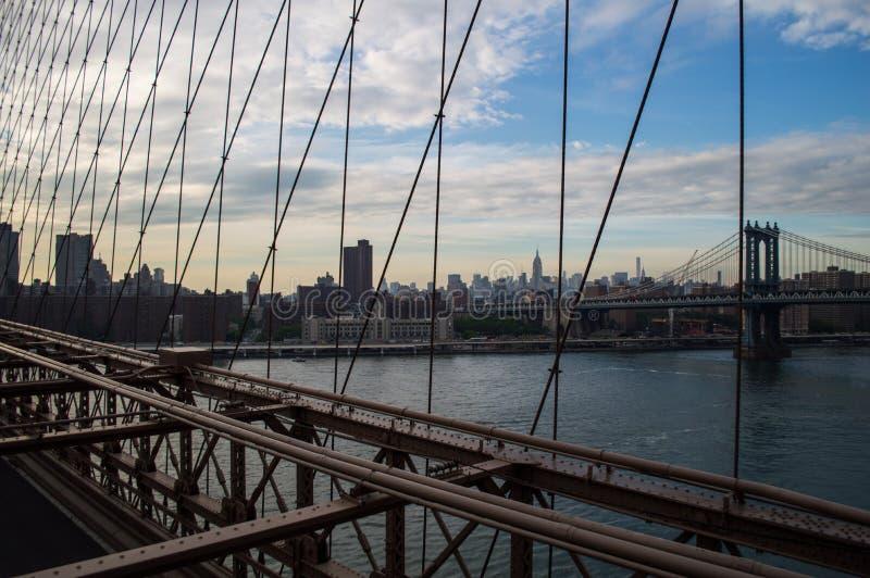 Horizonte de Midtown Manhattan en Nueva York según lo visto del puente de Brooklyn en la oscuridad fotos de archivo